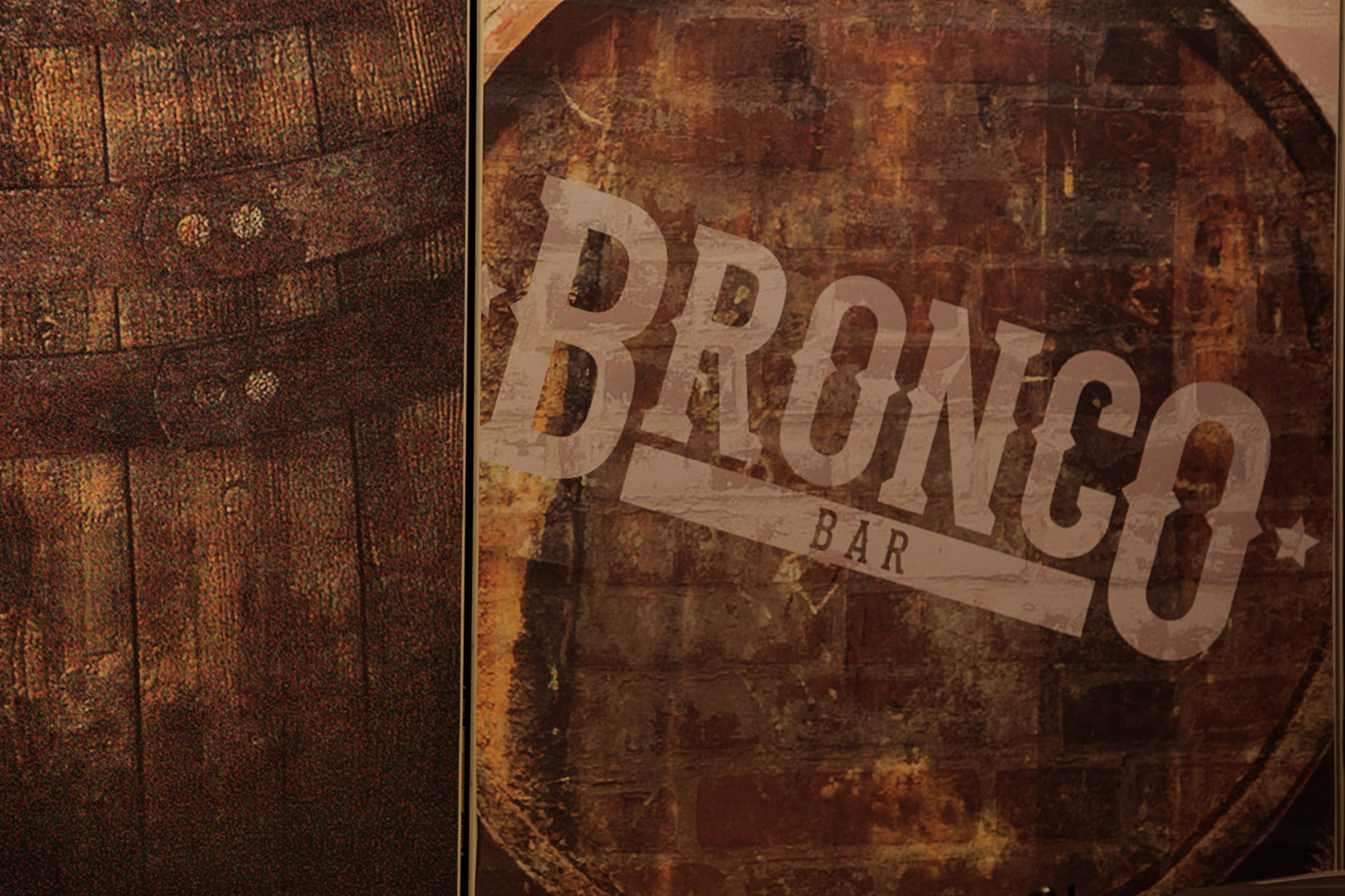 Bronco Bar logo on old wood barrels